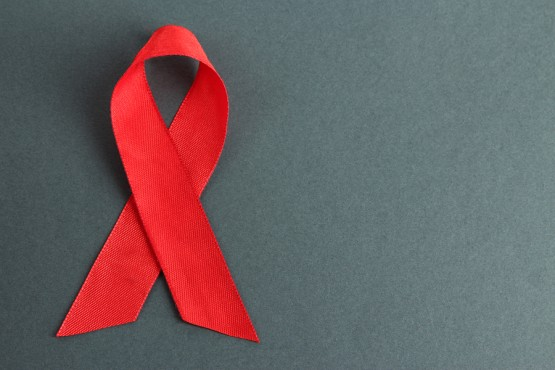 Red ribbon HIV, AIDS on gray background
