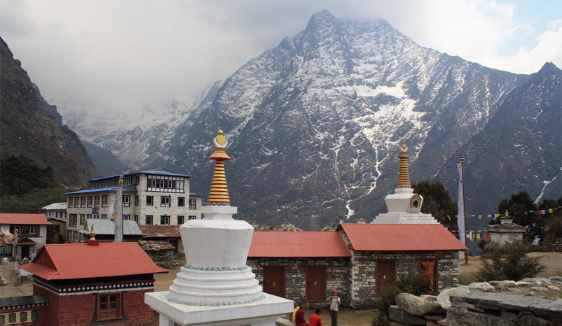 Everest behind a Sherpa village. The Sherpa people have a long history of serving as mountain guides for those who want to reach the summit of the mountain and who can afford an expedition.