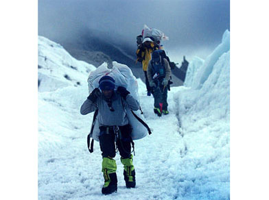 Nepalese Sherpas with luggage make their way through the Khumbu Icefall to Everest base camp, Nepal.