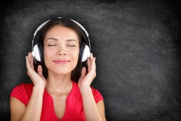 Music in headphones. Beautiful young Asian woman with her eyes c