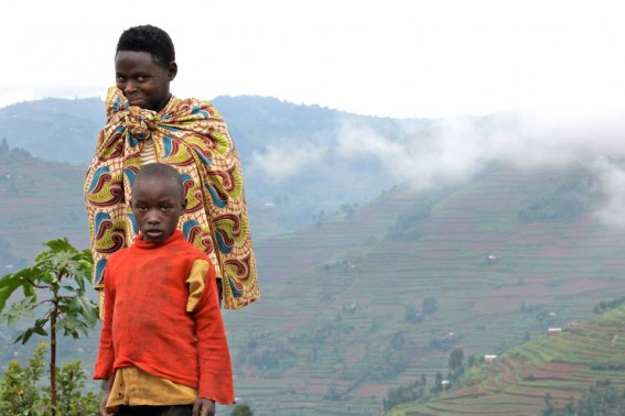 A sister and brother watch me, as I snap a portrait. Rolling Rwandan hills in the backdrop…