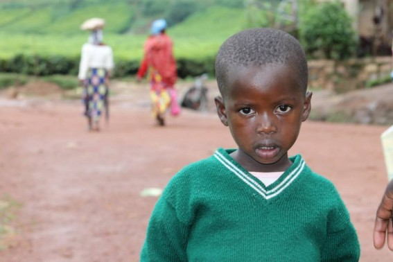 A child watches me snap a photo, as we make our way through a remote Rwandan village.