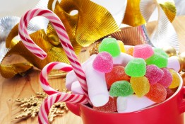 a bowl with different candies, such as candy canes, on a table w
