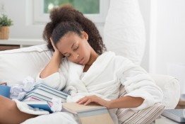 Young African female student falling asleep with a book