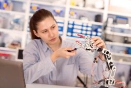 schoolgirl adjusts the robot arm model, girl in a robotics labor