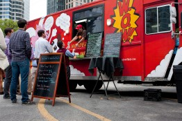 Customers Wait In Line To Order Meals From Food Truck