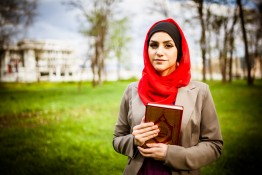 Muslim woman wearing hijab and holding the Koran ** Note: Shallow depth of field
