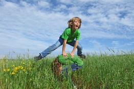 happy kids or children playing leapfrog outdoors in summer