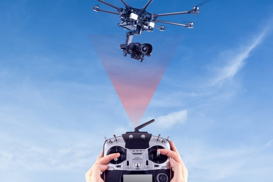 Hands of a man with a radio control drone on a background of beautiful blue sky. Remote radio control copter in the young man's hands. Management of professional drone