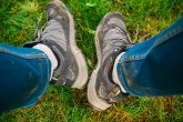 Legs in dirty shoes and jeans while hiking. Active holiday in the mountains