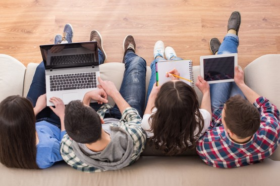 Top view of a four young people students are sitting on sofa with laptop and tablet are studying.
