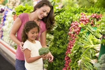 Mother and daughter shopping for broccoli at a grocery store