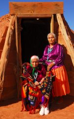 Elderly 99 year old Navajo Native American woman and her daughter standing in front of a traditional Hogan