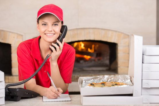 Smiling delivery young woman of pizza on the phone. The boxes of pizza on the table. ** Note: Shallow depth of field