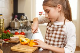 Young teenage girl in apron cutting sweet pepper on board at the kitchen.