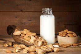 Almond milk with almond on a wooden table