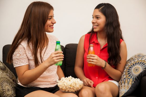 Cute couple of teenage girlfriends drinking soda and eating popcorn before watching a movie