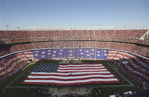 A U.S. flag is presented on the field at Levi's Stadium as Pat Monahan of the music group Train sings the national anthem before an NFL football game between the San Francisco 49ers and the Chicago Bears in Santa Clara, Calif., Sunday, Sept. 14, 2014. (AP Photo/Noah Berger)