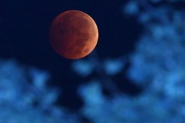 The Earth's shadow renders the moon during a total lunar eclipse over Milwaukee on late Tuesday, Oct. 7,  2014.  The moon appears orange or red, the result of sunlight scattering off Earth's atmosphere. This is known as the blood moon.  (AP Photo/Milwaukee Journal-Sentinel, Mike De Sisti)