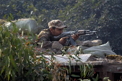 A Pakistani army soldier takes position on a bunker close to a school under attack by Taliban gunmen in Peshawar, Pakistan, Tuesday, Dec. 16, 2014. The attack began in the morning when the gunmen entered the school and started shooting at random. Army commandos quickly arrived at the scene and started exchanging fire with the gunmen. Students wearing green school uniforms could be seen fleeing the area on Pakistani television.(AP Photo/Mohammad Sajjad)