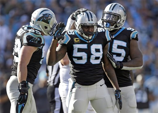 FILE - In this Dec. 13, 2015, file photo, Carolina Panthers' Thomas Davis (58) celebrates after a play against the Atlanta Falcons with Luke Kuechly (59) and Charles Johnson (95) in the first half of an NFL football game in Charlotte, N.C. After overcoming three torn ACLs to the same knee and battling 11 years to get to the Super Bowl, it almost seems cruel that Davis will have to play the biggest game of his life with a broken arm. But the former NFL Walter Payton Man of the Year is used to overcoming adversity. (AP Photo/Bob Leverone, File)